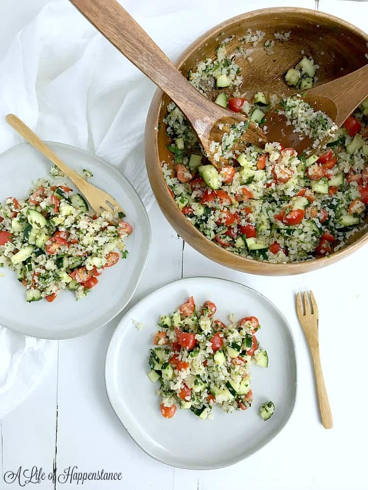 A brown bowl filled with cauliflower tabbouleh and two white plates with tabbouleh.