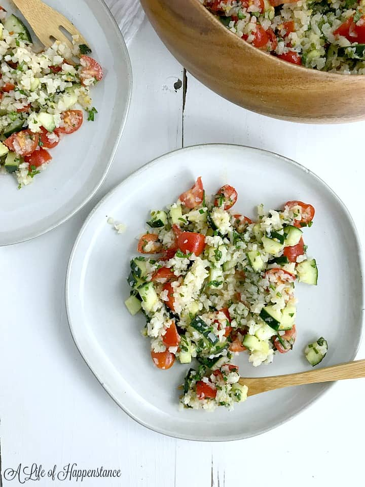 Two white plates with cauliflower tabbouleh.