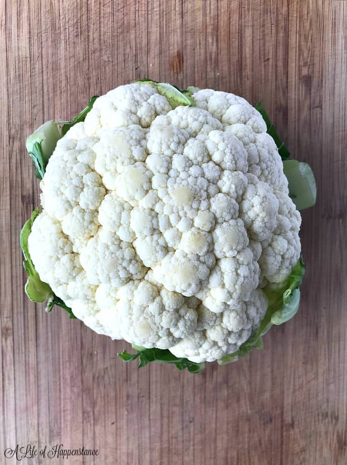 A medium head of cauliflower on a cutting board.