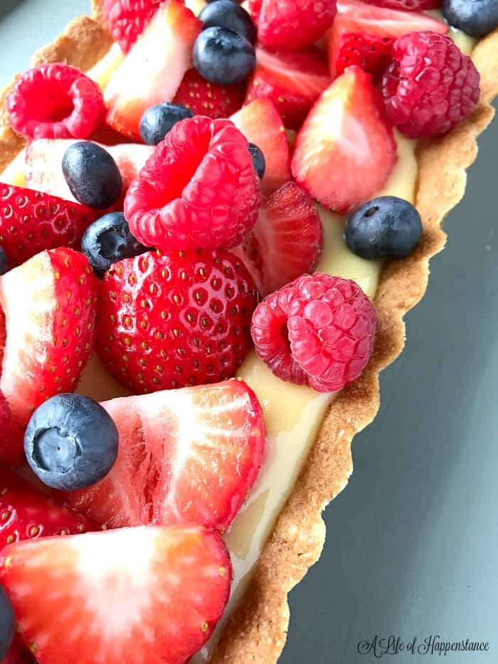A closeup of a Paleo lemon tart topped with fresh berries.