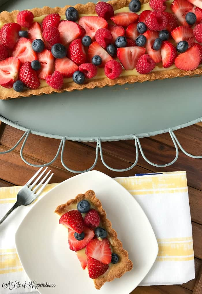 The Paleo lemon tart topped with fresh berries on a serving tray with a slice on a white plate.