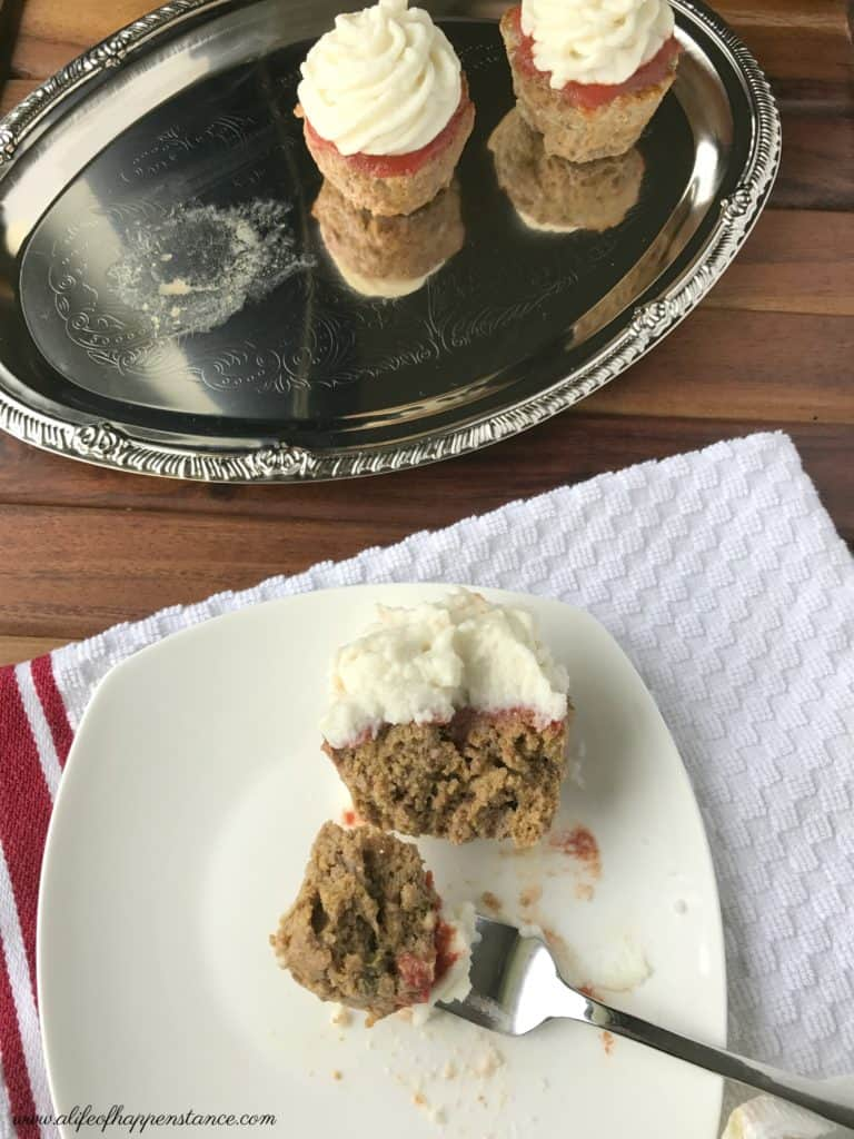 A meatloaf cupcake on a white plate with part on a fork.