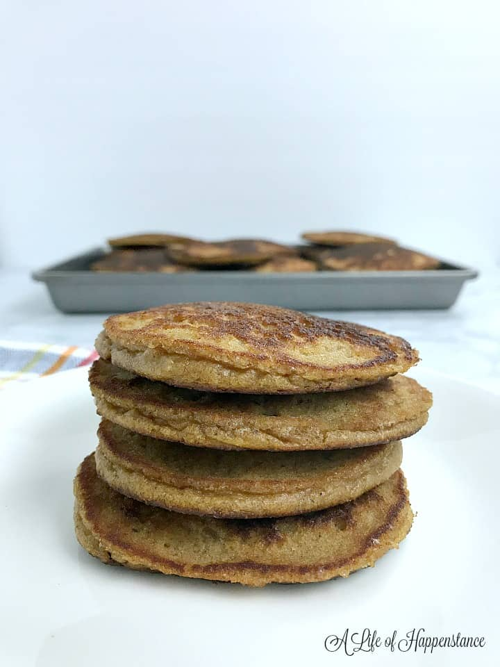 A white plate with a stack of four almond flour pumpkin pancakes on it.