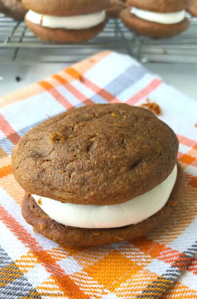 An assembled SCD and Paleo Pumpkin Whoopie Pie on an orange and white checkered kitchen towel.