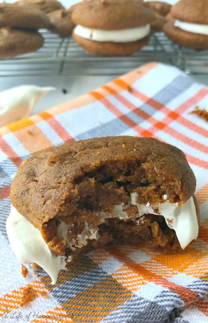 A paleo and scd pumpkin whoopie pie with a big bite taken out of it.
