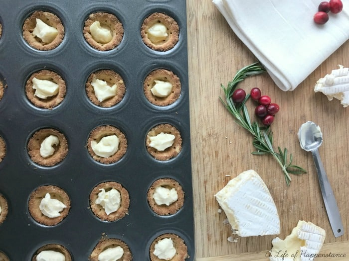Filling the pre baked tartlets with brie cheese.