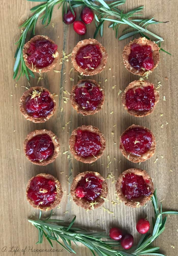 Rosemary Infused Cranberry Brie Tartlets on a wooden cutting board.