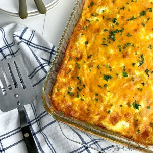 The make ahead breakfast egg casserole in a clear glass baking dish on a blue and white kitchen towel.