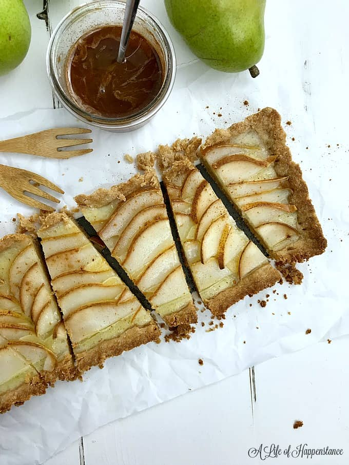 Pear almond tart sliced on a piece of parchment paper.