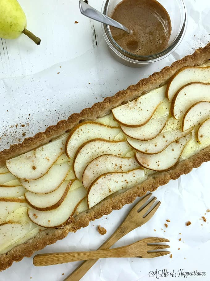The baked pear almond tart dusted with ground cinnamon.