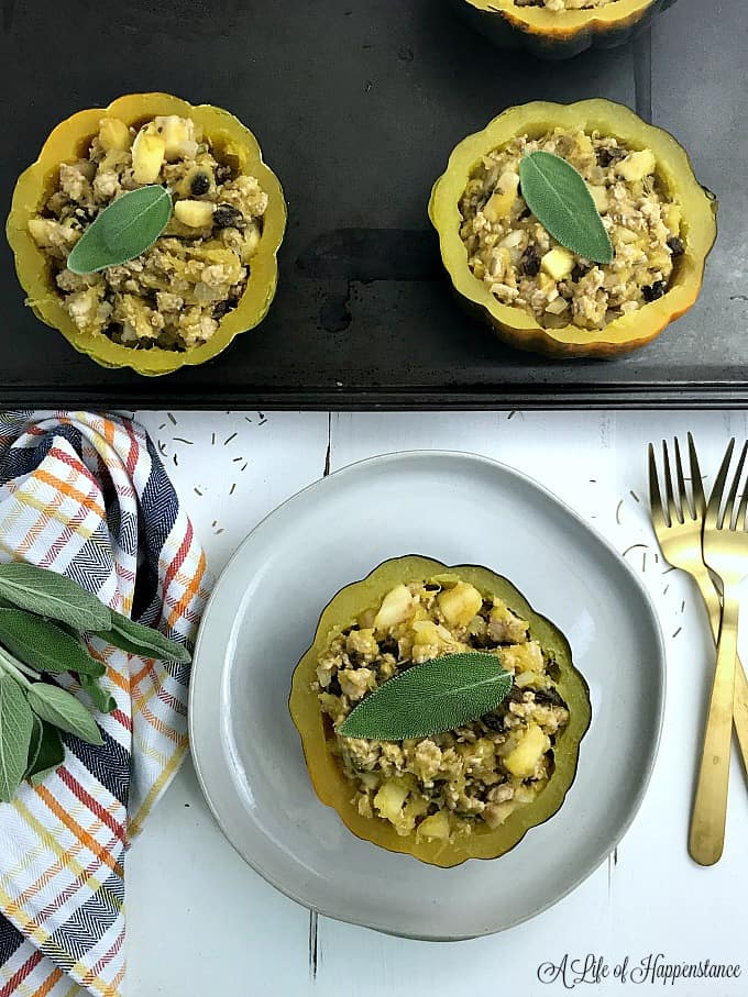 One turkey filled acorn squash on a white plate with the rest on a baking sheet.