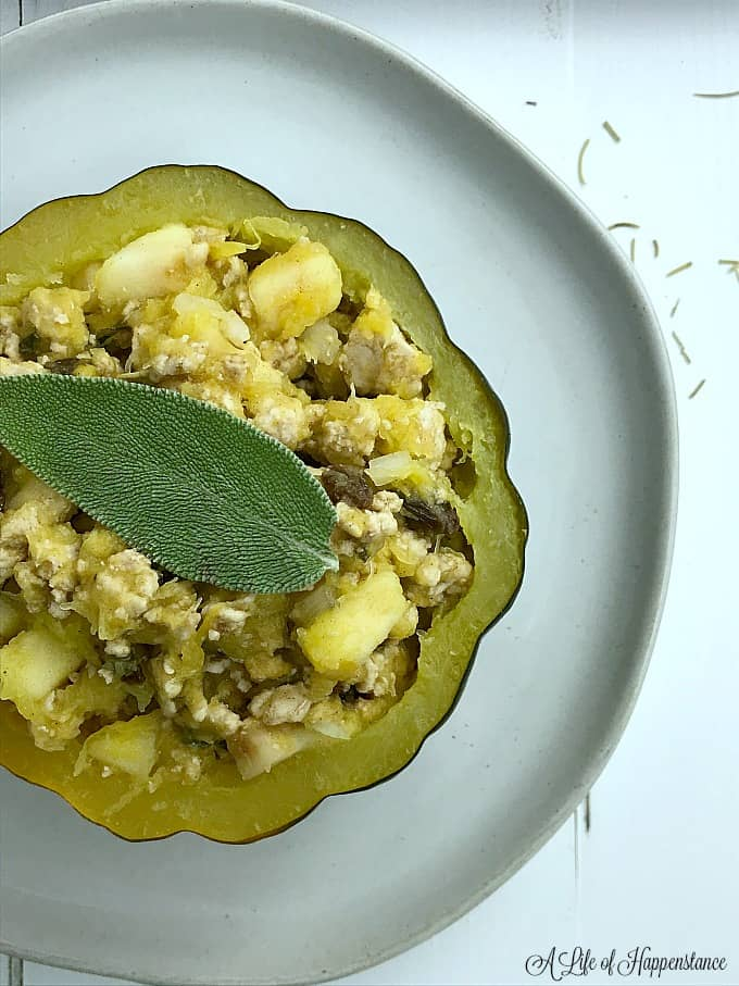 A close up of a turkey stuffed acorn squash garnished with a sage leaf.