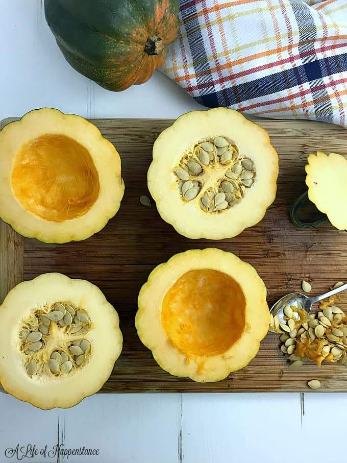 Acorn squash cut in half and seeded on a cutting board.
