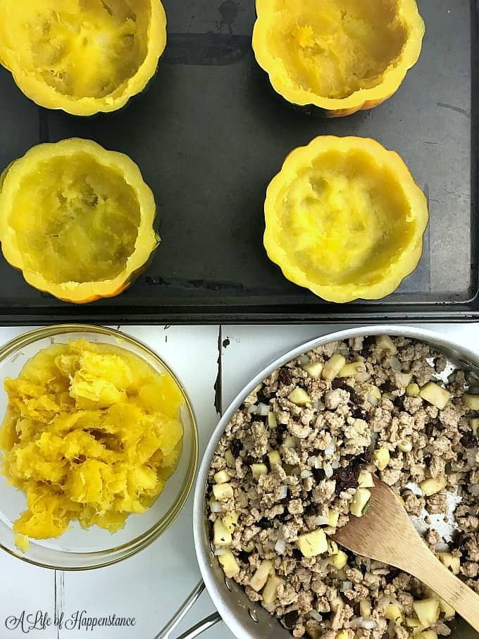 Hollowed out acorn squash with a pan filled with ground turkey.