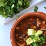 A small bowl of soup garnished with chopped avocado and cilantro. Cilantro and lime wedges in the background.