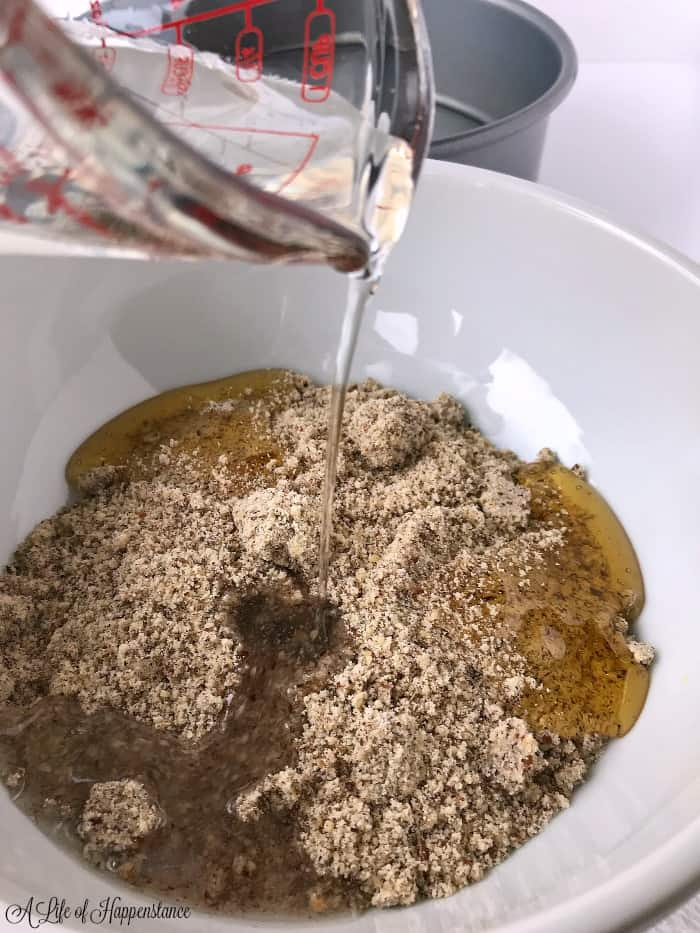 Melted coconut oil being poured into a white bowl full of hazelnut meal, honey and lemon juice.