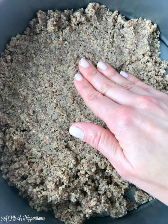 Hazelnut crust dough being pressed into the bottom of a springform pan.