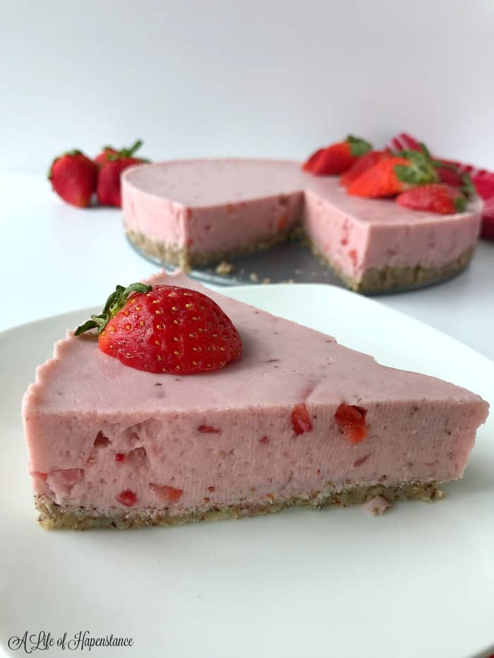 A Close up of a piece of strawberry gelatin pie garnished with a strawberry. The whole pie in the background.