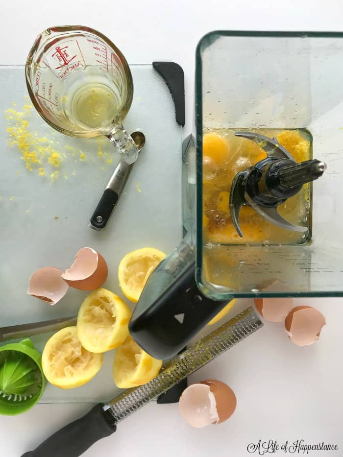 Overhead photo of a blender filled with ingredients for the paleo lemon cake. Around the blender are lemons, egg shells and utensils.