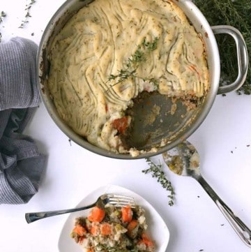 An overhead picture of the skillet filled with warm shepard's pie. Some of the pie has been placed on a small white plate.