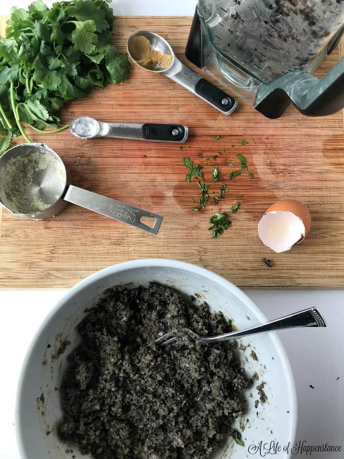A white bowl of mashed black beans and a brown cutting board with cilantro and measuring spoons on top.
