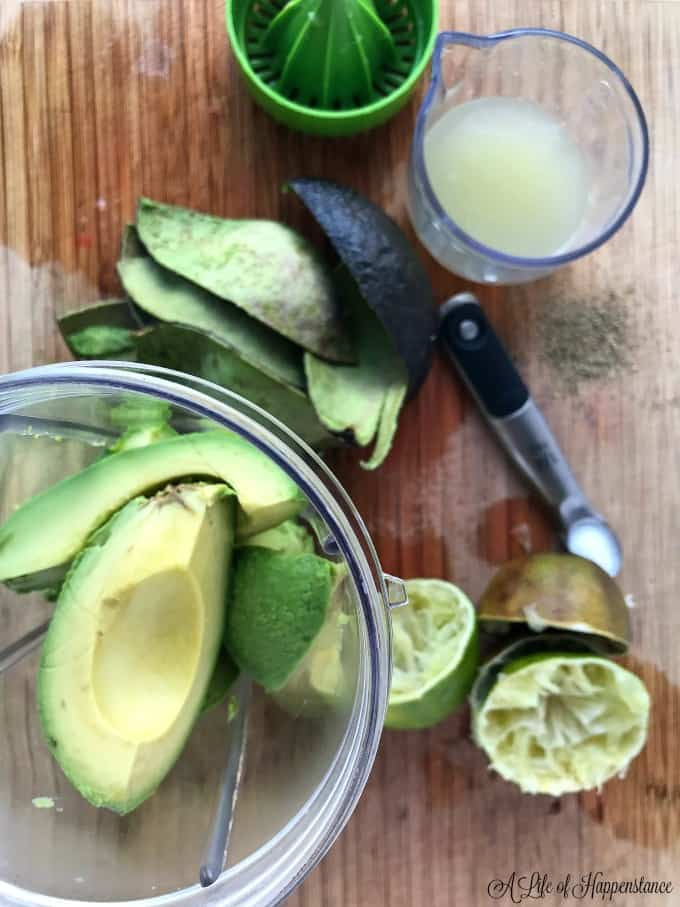 A blender jar filled with avocado. A cutting board with a cup of fresh lime juice and limes.