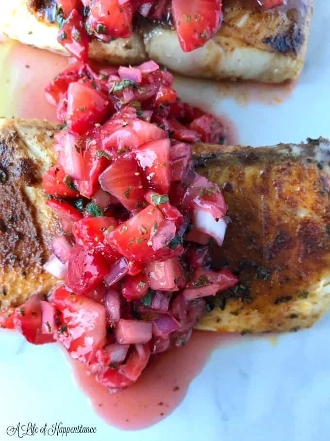 Close up of a seared mahi mahi fillet with strawberry mint salsa on top.