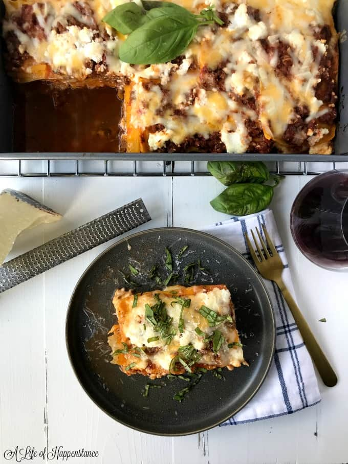 Overhead shot of a pan of butternut squash lasagna. A plate with a large slice of lasagna.