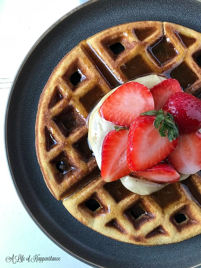 Close up of a coconut flour waffle on a grey plate. The waffle is topped with cashew cream, fresh berries and cinnamon honey syrup.