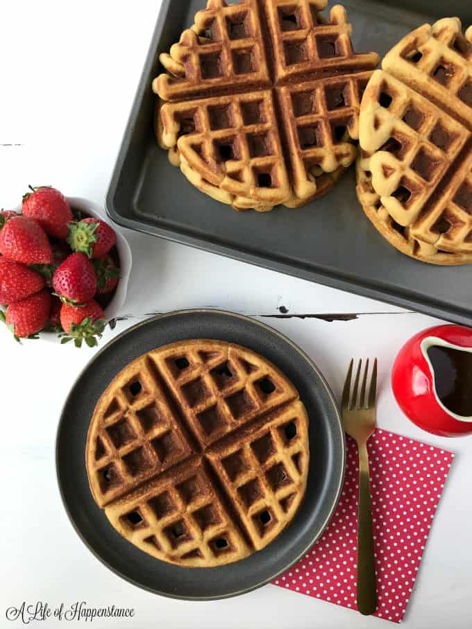 Waffles in a baking tray. One waffle on a grey plate with a small bowl of strawberries.