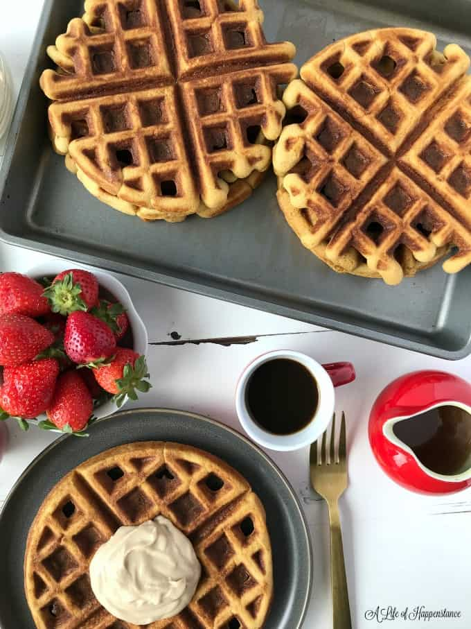 Waffles in a baking tray. One waffle on a grey plate topped with cashew cream. The table also has a bowl of strawberries and mug of coffee.