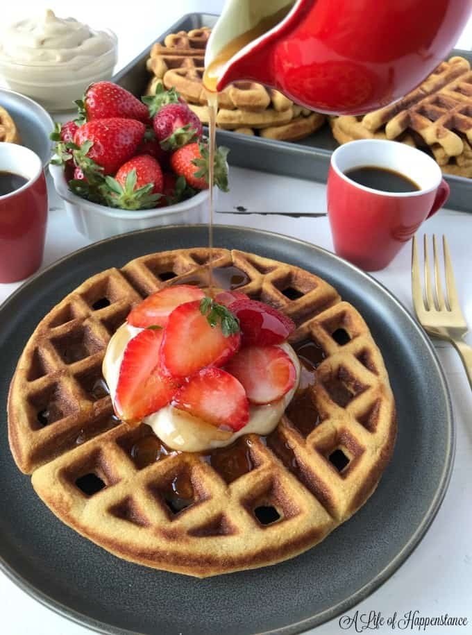 Waffles in a baking tray. One waffle on a grey plate topped with cashew cream and strawberries. Cinnamon honey syrup is being poured on top.