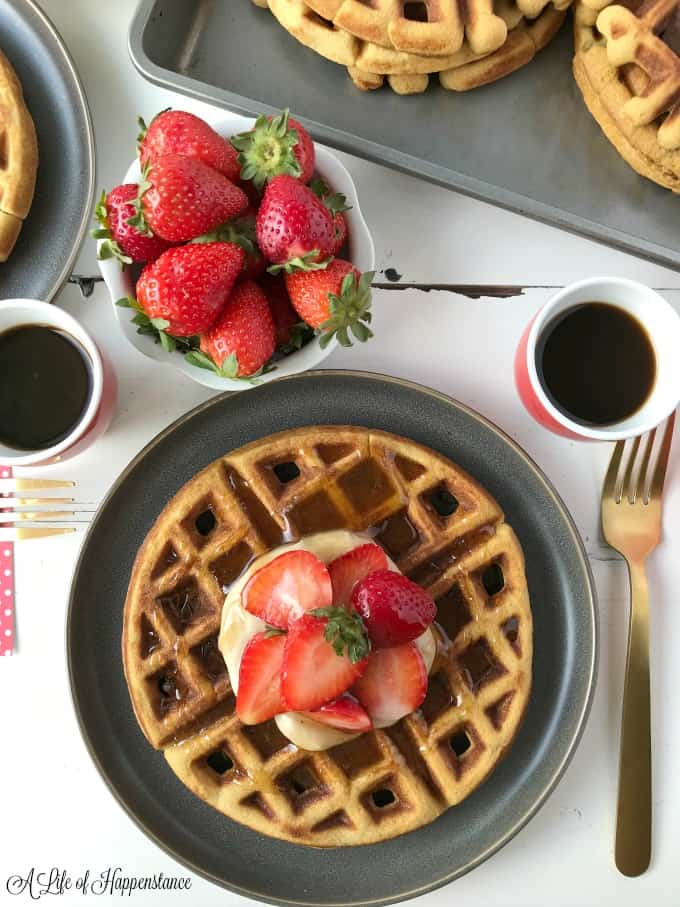 Waffles in a baking tray. One waffle on a grey plate topped with cashew cream, strawberries and cinnamon honey syrup.