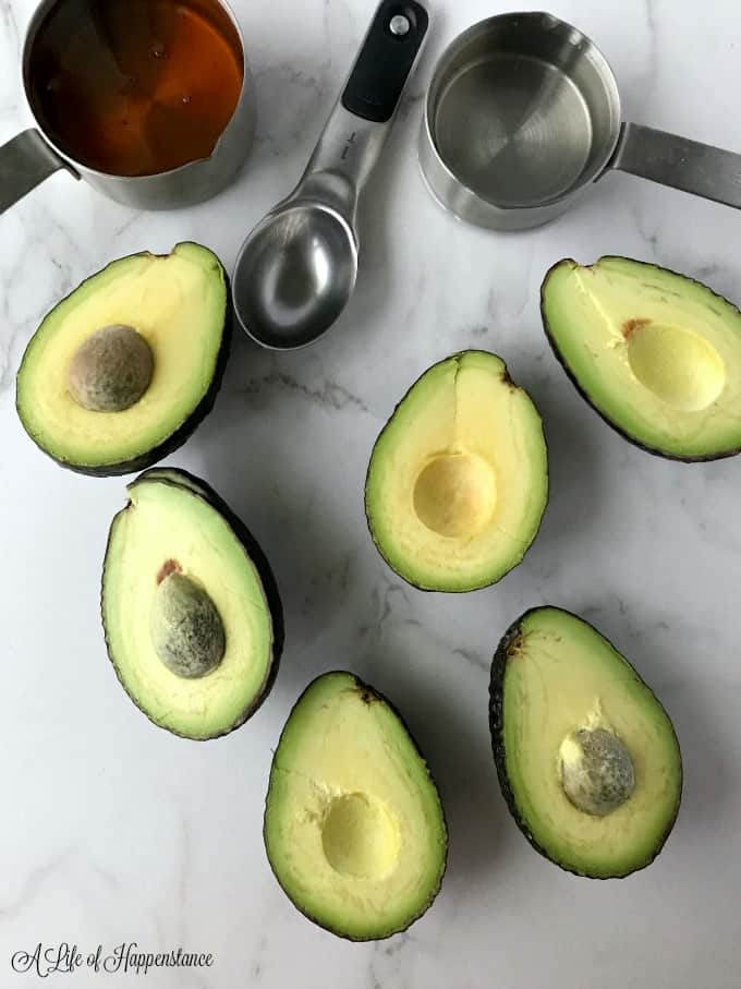 A marble cutting board with avocados sliced open and measuring cups with honey and coconut oil.