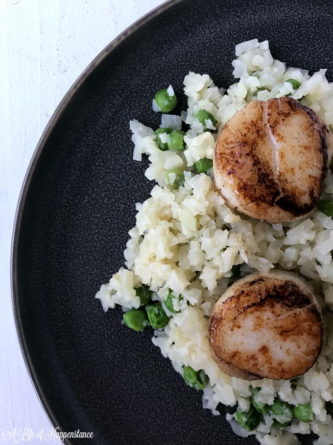 Seared scallops with Parmesan cauliflower risotto on a black plate.