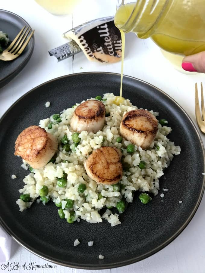 Drizzling the citrus vinaigrette over a plate of seared scallops and Parmesan cauliflower risotto.