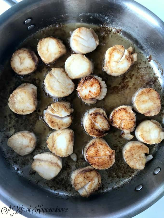 The scallops searing in a saute pan.