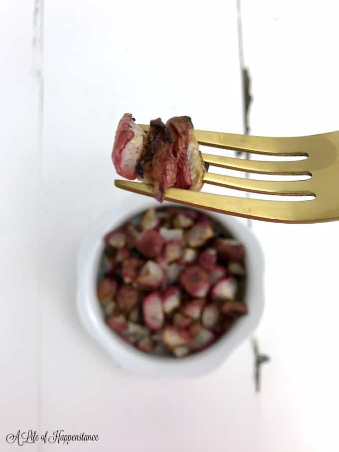 Close up of roasted radishes on a gold fork. The rest of the radishes are in a white bowl in the background.