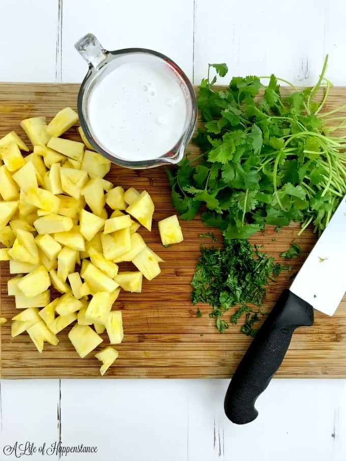 A wood cutting board with chopped pineapple, cilantro and a measuring cup filled with coconut milk on top.