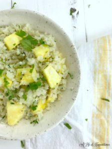 A white bowl filled with coconut cauliflower rice and pineapple.