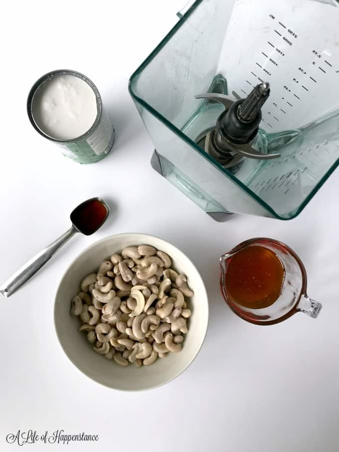 A can of coconut milk, vanilla extract, bowl of cashews, and cup of honey surrounding a blender.