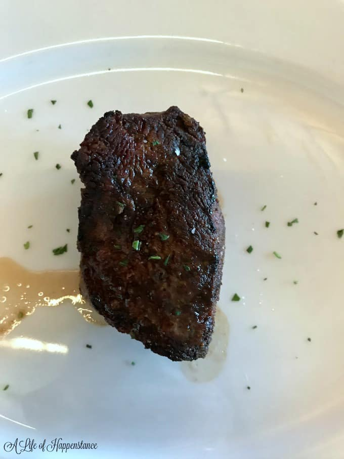 A 6 oz filet mignon on a white plate from Ocean Prime.