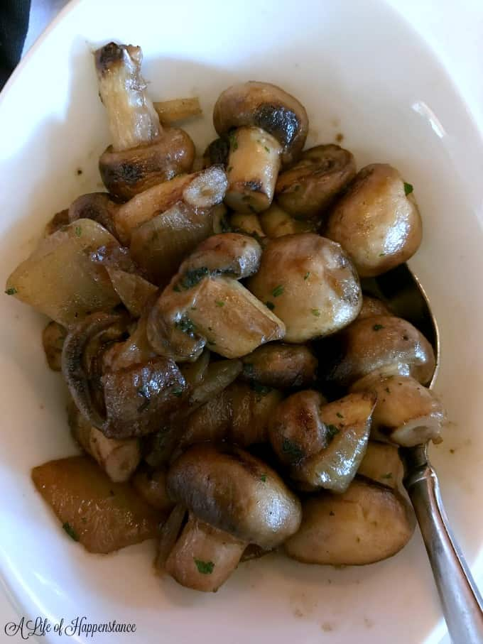 I white bowl filled with sauteed button mushrooms from Ocean Prime Tampa.