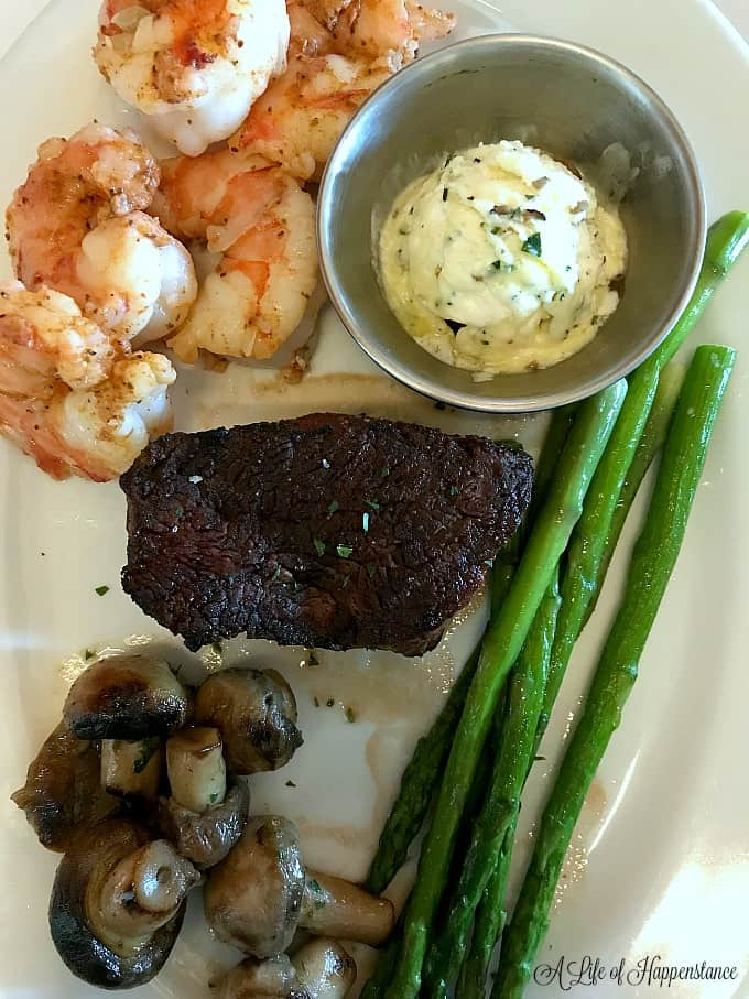 A white plate filled with shrimp, asparagus, filet mignon, and button mushrooms from Ocean Prime Tampa.