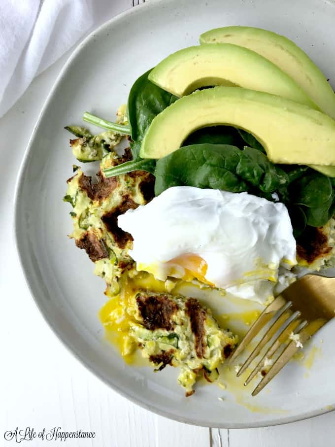 A white plate filled with a summer squash waffle, poached egg, baby spinach, and avocado.