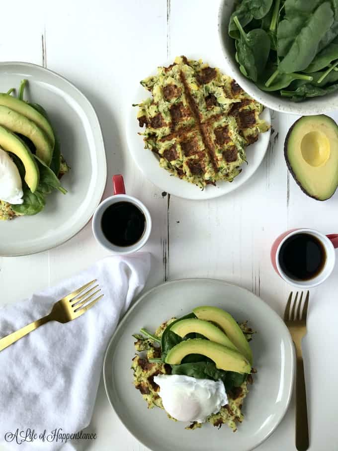 Breakfast table set with plates of summer squash waffles, poached eggs, spinach, avocado, and coffee.