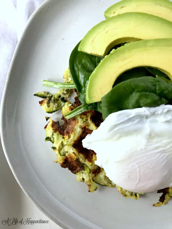 A white plate piled high with a summer squash waffle, poached egg, spinach, and avocado.