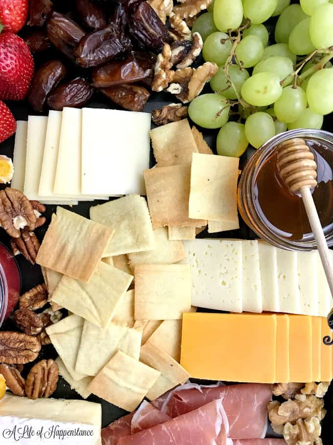 Almond flour crackers on a cheese, fruit, and meat board.