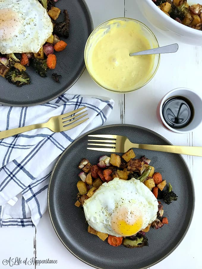 Two plates filled with roasted vegetables and topped with eggs over easy.