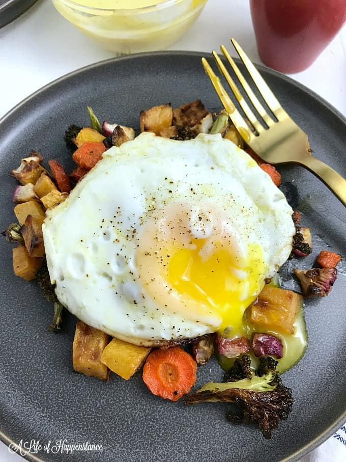 A grey plate filled with roasted vegetables and topped with an egg.